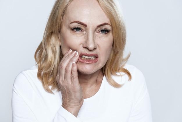 La mujer tiene un dolor de muelas. ella se siente mal.
