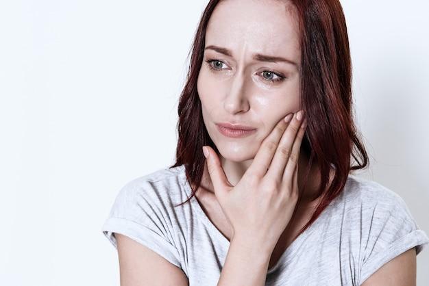 La mujer tiene un dolor de muelas sobre fondo blanco.