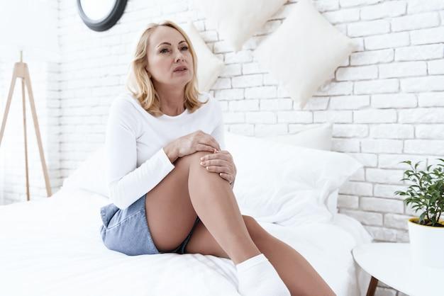 La mujer tiene un dolor de rodilla, ella está haciendo un masaje.