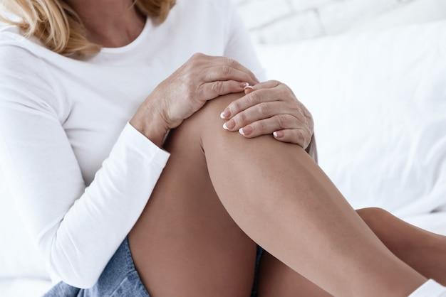 Una mujer tiene un dolor en la rodilla, ella está haciendo un masaje.