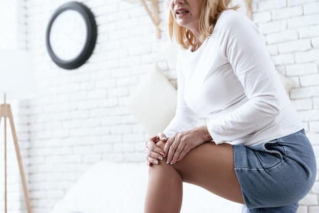 Una mujer tiene dolor de rodilla, está haciendo un masaje.