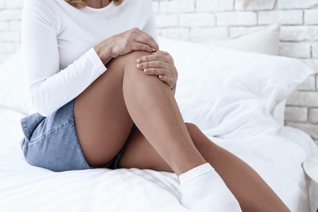 La mujer tiene dolor de rodilla, está haciendo un masaje.