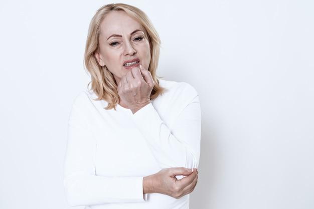 Una mujer tiene un dolor en su brazo sobre fondo blanco.