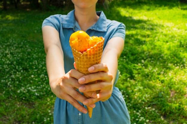 Mujer tiene un helado en sus manos. helado de mango en un cono de waffle
