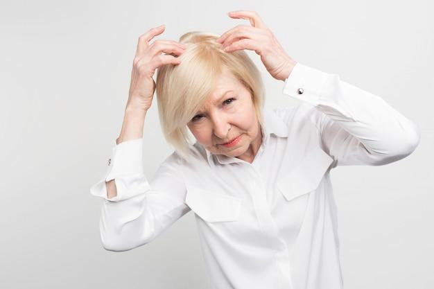 Esta mujer tiene el problema de perder el cabello de su cabeza. ella necesita un tratamiento. de lo contrario, necesitaría comenzar a usar una peluca lo antes posible.