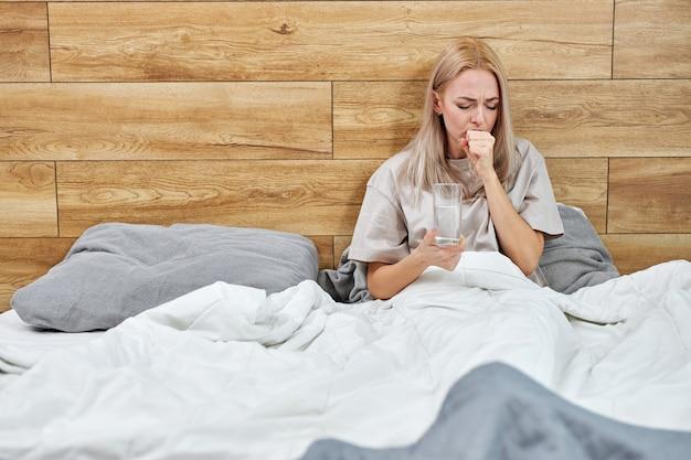 La mujer tiene síntomas respiratorios fiebre, tos, dolor de cuerpo sentada en la cama sola en casa, sufriendo una enfermedad grave. cuarentena, autoaislamiento, concepto de atención médica