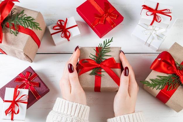 Mujer tiene en sus manos hermosa caja de regalo con lazo rojo