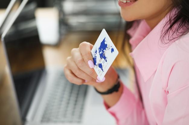 Mujer tiene tarjeta bancaria de plástico junto al portátil