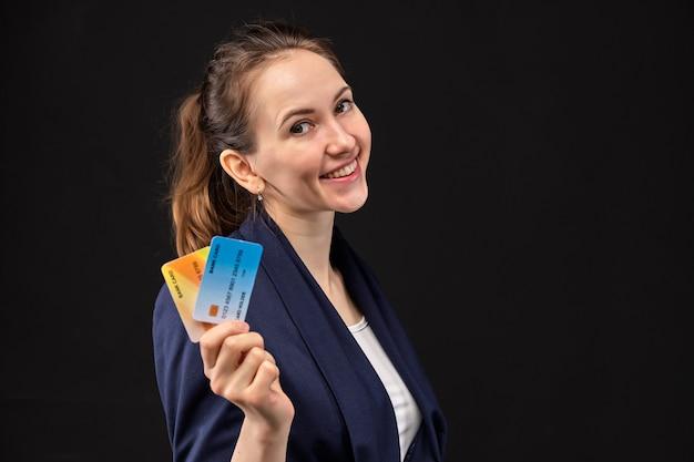 Mujer tiene tarjetas de crédito bancarias en sus manos y se ve sonriente.