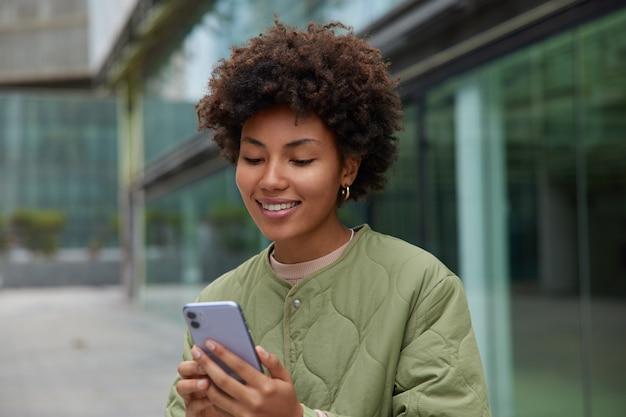 Mujer tiene videollamada sostiene teléfono móvil hace buen contenido multimedia para compartir en redes sociales graba vlog vestida con chaqueta lee texto de contenido