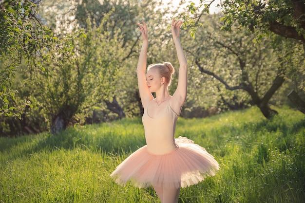 Mujer tierna bailarina en paisaje de flores verdes al atardecer