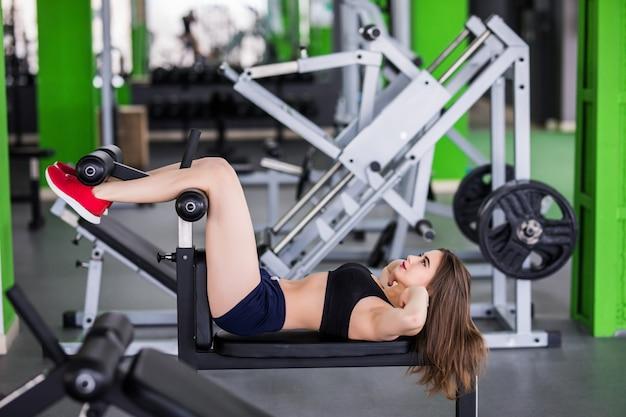 Mujer tierna hace ejercicios de prensa en simulador deportivo para su cuerpo en forma en el gimnasio moderno