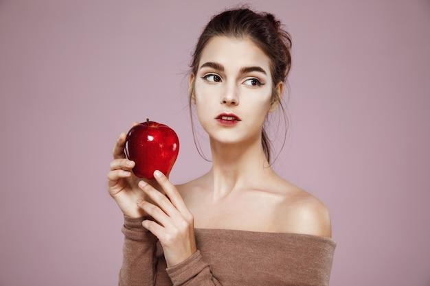 Mujer tierna joven que sostiene la manzana roja en rosa