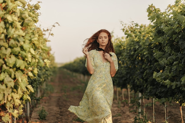 Mujer tierna con peinado ondulado rojo y vendaje negro en el cuello con un vestido largo y elegante de verano mirando al frente en un viñedo