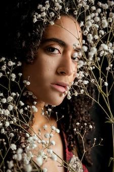 Mujer tierna con ramitas de flores cerca de la cara
