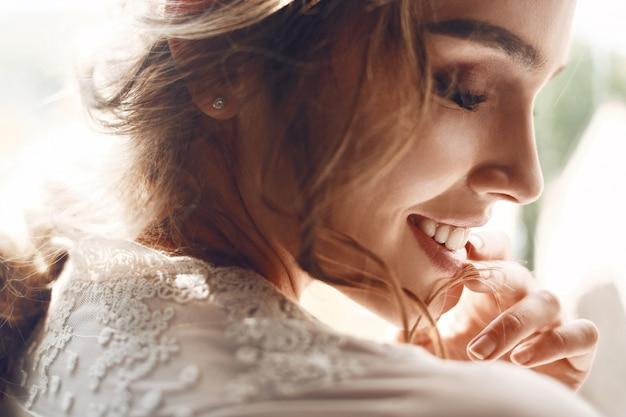 Mujer tierna en vestido blanco se inclina la barbilla hacia el hombro