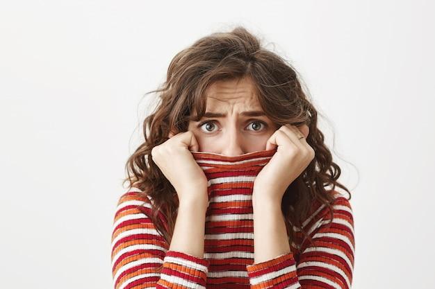 Mujer tímida asustada temblando y escondiendo la cara dentro del cuello del suéter