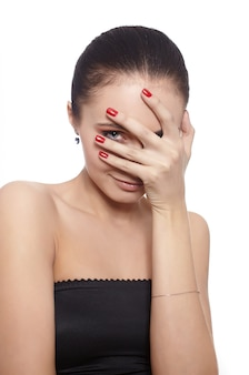 Mujer tímida cubriéndose la cara con la mano aislada en blanco
