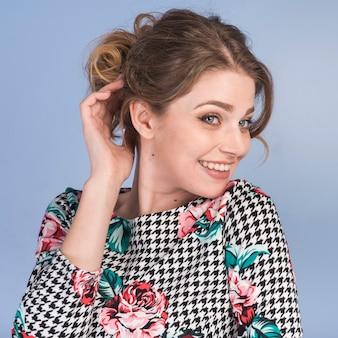 Mujer tímida sonriente en el vestido que sostiene el pelo