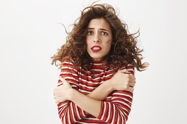Mujer tímida temblando tratando de calentar, sintiendo frío en clima ventoso