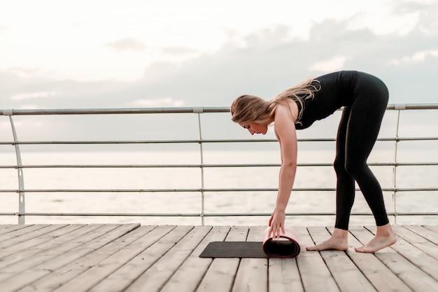La mujer tira la estera de yoga antes del entrenamiento de asanas en el mar al amanecer