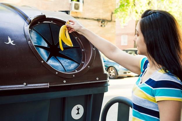 Mujer tirando una cáscara de plátano a la basura