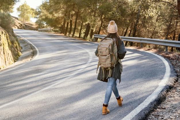 Mujer de tiro completo caminando por la carretera