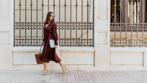 Mujer de tiro completo caminando con portátil