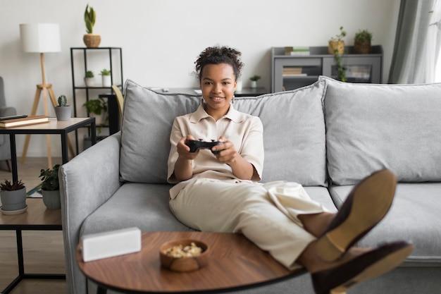 Mujer de tiro completo con controlador en el sofá