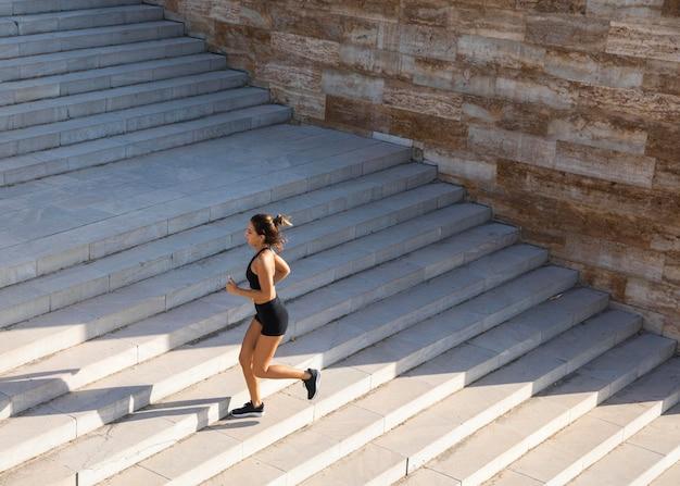 Mujer de tiro completo corriendo en las escaleras