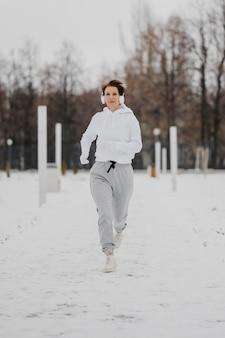 Mujer de tiro completo corriendo en la nieve