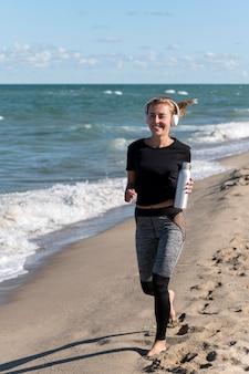 Mujer de tiro completo corriendo en la orilla