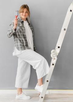 Mujer de tiro completo con escalera