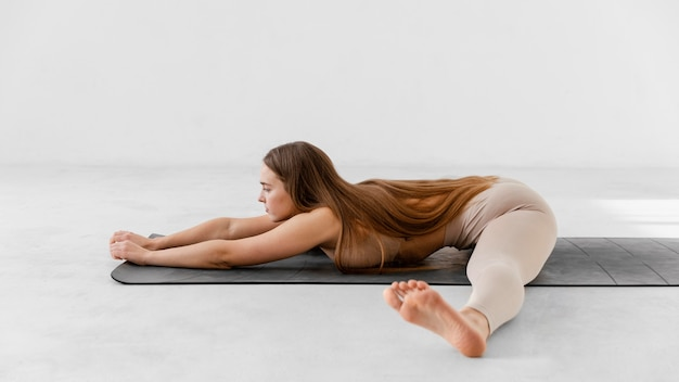 Mujer de tiro completo en estera de yoga