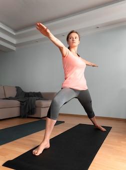 Mujer de tiro completo con estera de yoga