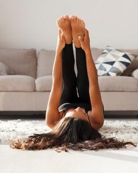 Mujer de tiro completo estirando las piernas