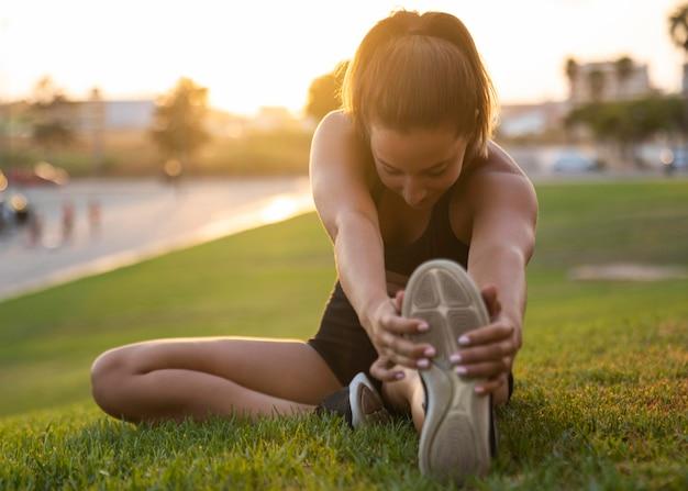 Mujer de tiro completo estirando su pierna