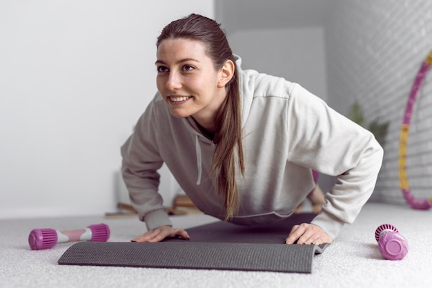 Mujer de tiro completo haciendo flexiones