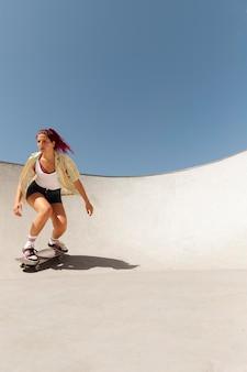 Mujer de tiro completo haciendo trucos en patineta