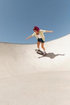 Mujer de tiro completo haciendo trucos en skate