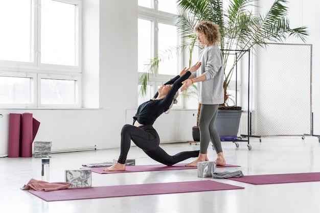 Mujer de tiro completo haciendo yoga con el profesor en el interior