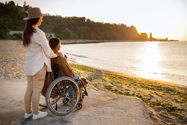 Mujer de tiro completo y hombre discapacitado viajando