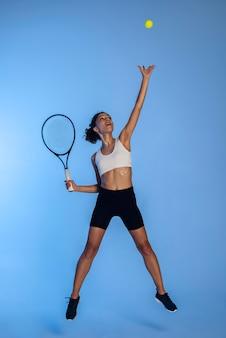 Mujer de tiro completo jugando al tenis