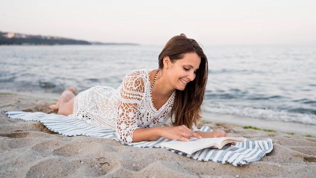 Mujer de tiro completo leyendo sobre una manta