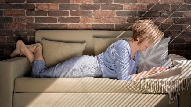 Mujer de tiro completo leyendo en el sofá