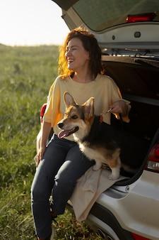 Mujer de tiro completo con lindo perro y coche