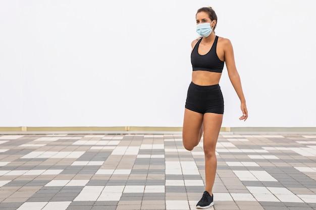 Mujer de tiro completo con máscara de estiramiento