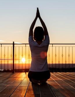 Mujer de tiro completo meditando al aire libre