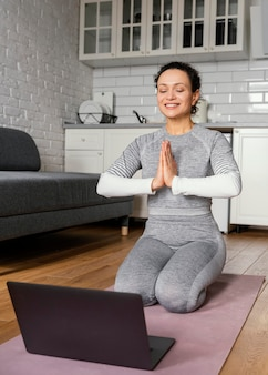 Mujer de tiro completo meditando sobre estera