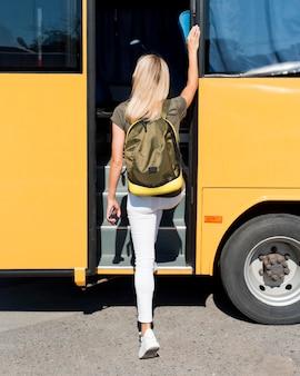 Mujer de tiro completo con mochila subirse al autobús